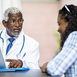 A senior black doctor explaining something on a tablet to a young black womanA senior black doctor explaining something on a tablet to a young black woman