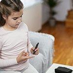 Teenage girl checking her blood sugar level
