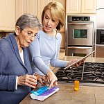 Young woman helping senior in kitchen to sort her medications