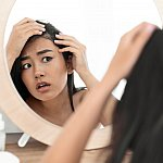 Troubled young Asian woman checking for thinning hair in mirror