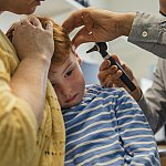 Boy's ear being examined by a doctor with an otoscope