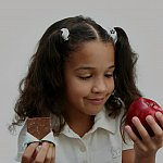 A girl deciding what to eat, with chocolate in one hand and an apple in the other.