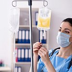Doctor preparing bag of blood plasma for patient