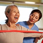 Woman using resistance band guided by physical therapist in rehab center