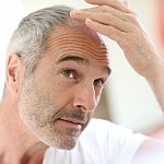 Older man looking at his hair in a mirror