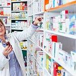 Woman pharmacist taking prescription drugs from shelf